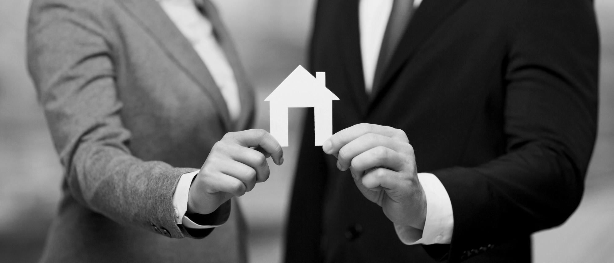 Hände halten Haus aus Papier - bildlich für Immobilienrecht, Mietrecht, Baurecht, Nachbarschaftsrecht & WEG-Recht in München